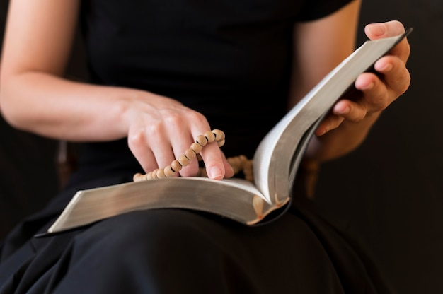 Person, die vom heiligen buch liest, während rosenkranz hält
