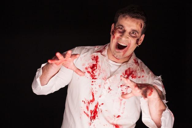 Person, die von einem zombie besessen ist, der auf schwarzem hintergrund mit blut bedeckt ist. halloweenkostüm.