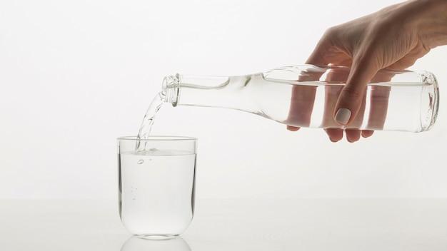 Person, die wasser in glas gießt