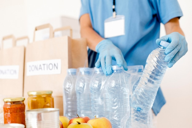 Person, die wasserflaschen in spendenbeutel steckt