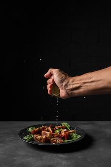 Person, die zitrone auf salat drückt