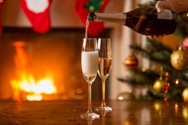 Person, die zwei gläser mit champagner füllt brennender kamin und geschmückter weihnachtsbaum im hintergrund