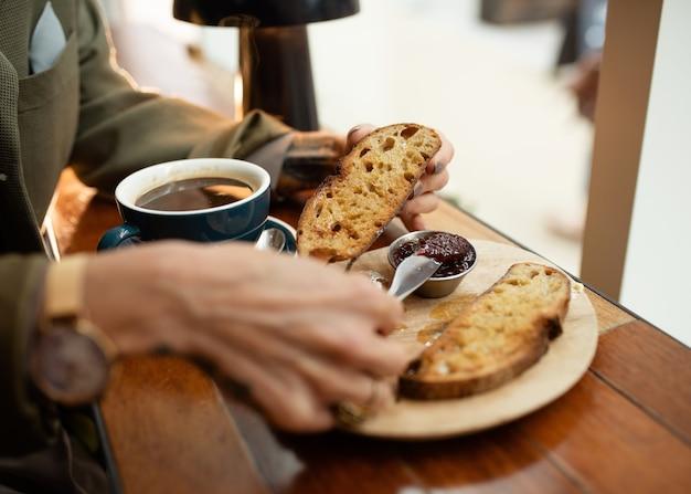 Person frühstückt mit kaffee und toast mit marmelade im café?