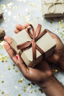 Person gibt ein geschenk, das mit ihrer eigenen hand gemacht wird