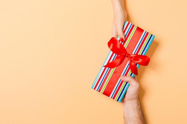 Person gibt geschenkbox mit roter schleife