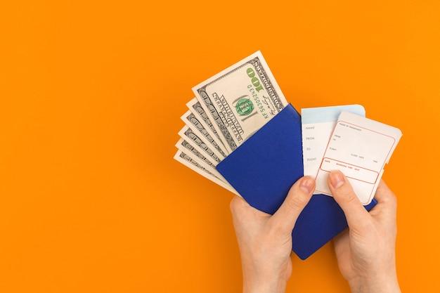 Person hält bordkarte mit geld und reisepass, reiseflachkonzepthintergrund mit kopienraumfoto