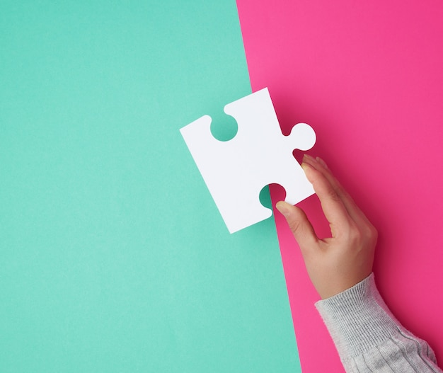 Person hält ein großes leeres weißes puzzlespiel über einer bunten oberfläche