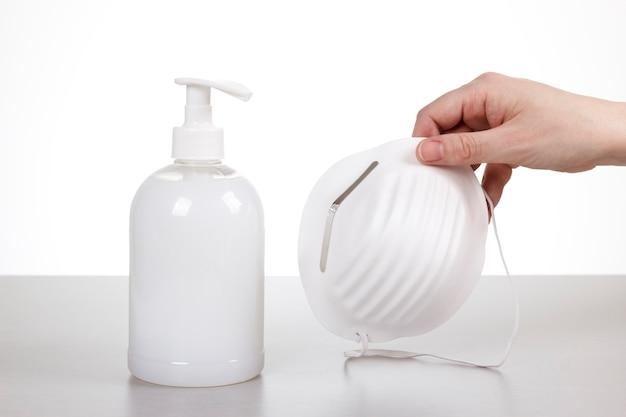 Person hält eine maske, nachdem sie die hände gründlich mit flüssigseife gewaschen hat