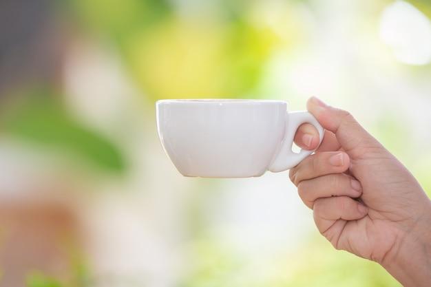 Person hält eine weiße kaffeetasse