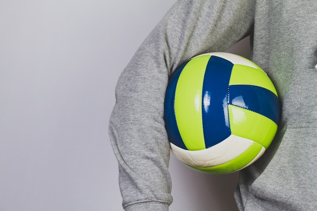 Person hält einen ball mit dem arm