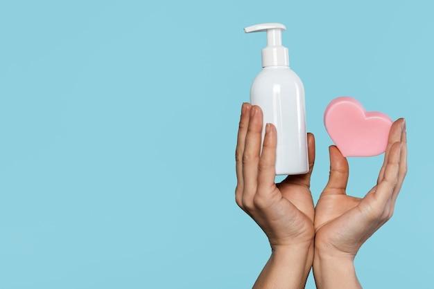 Person hält flasche mit desinfektionsmittel und seife