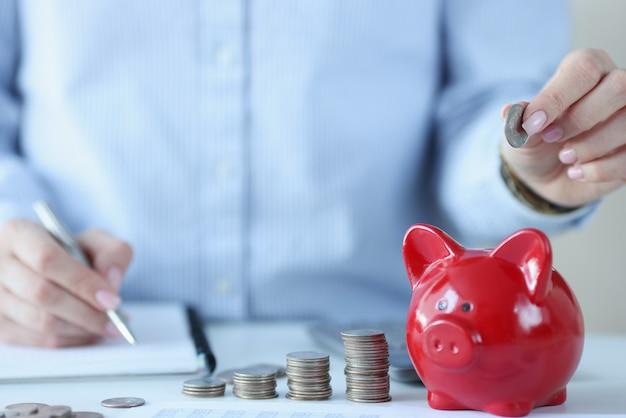 Person hält münzen über sparschwein und macht notizen in dokumenten