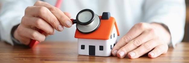 Person hört durch stethoskop auf wand und dach des hauses. immobilienversicherung gegen verlustrisiken und schadenkonzept