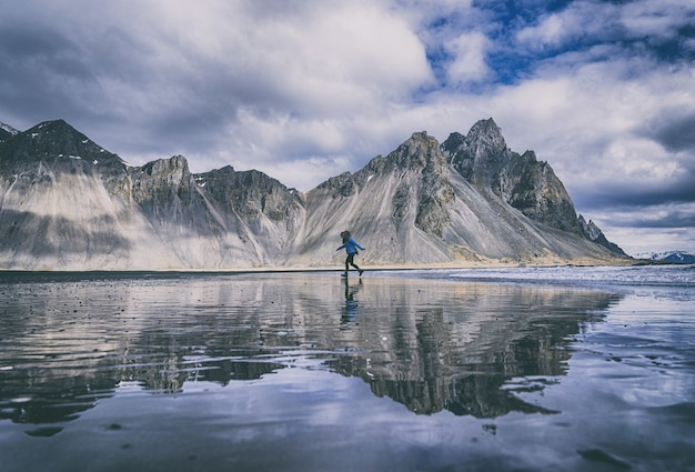Person im blauen hemd und in der schwarzen hose, die auf blauem kajak auf see nahe berg unter steht