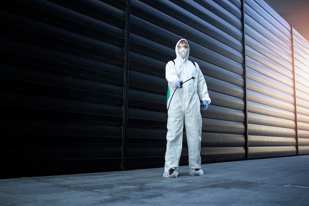 Person im weißen chemikalienschutzanzug, der desinfektion und schädlingsbekämpfung durchführt und gift sprüht, um insekten und nagetiere zu töten