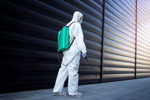Person im weißen chemikalienschutzanzug, die desinfektion und schädlingsbekämpfung mit sprühgerät durchführt, um insekten und nagetiere abzutöten
