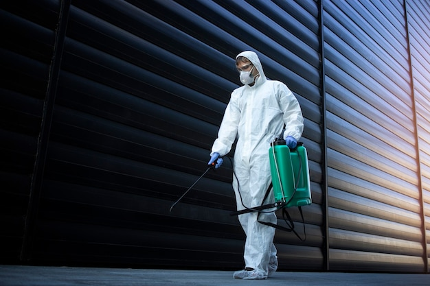 Person im weißen chemikalienschutzanzug, die öffentliche bereiche desinfiziert, um die ausbreitung des hoch ansteckenden koronavirus zu stoppen