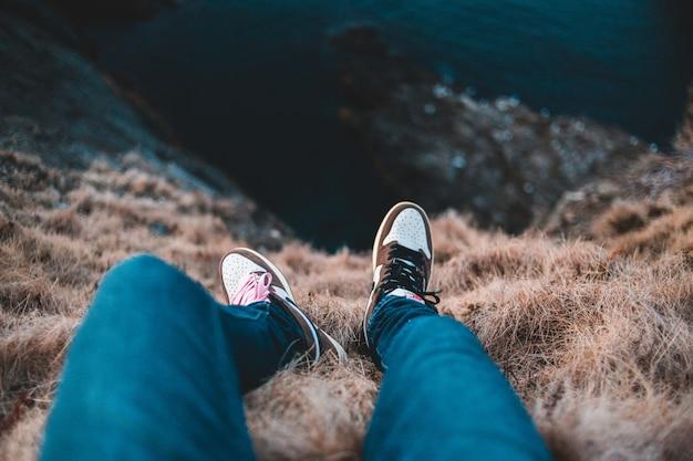 Person in blauen hosen und schwarzen und weißen turnschuhen, die tagsüber auf braunem grasfeld sitzen