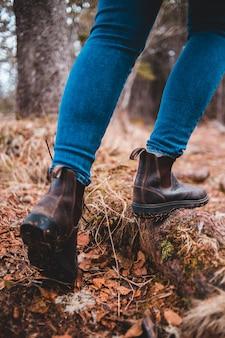 Person in blauen jeans und schwarzen lederstiefeln, die auf braunen getrockneten blättern stehen