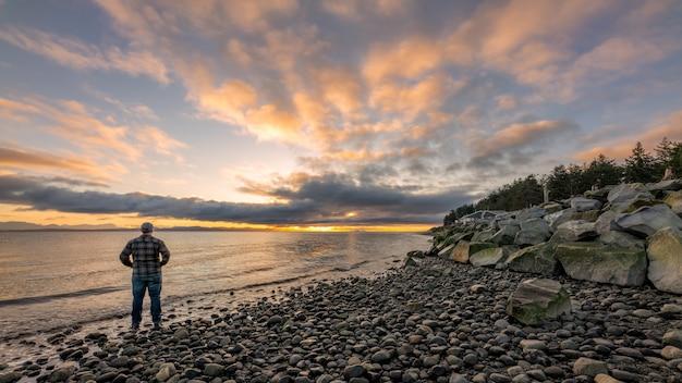 Person in der schwarzen jacke, die auf rocky shore während des sonnenuntergangs steht