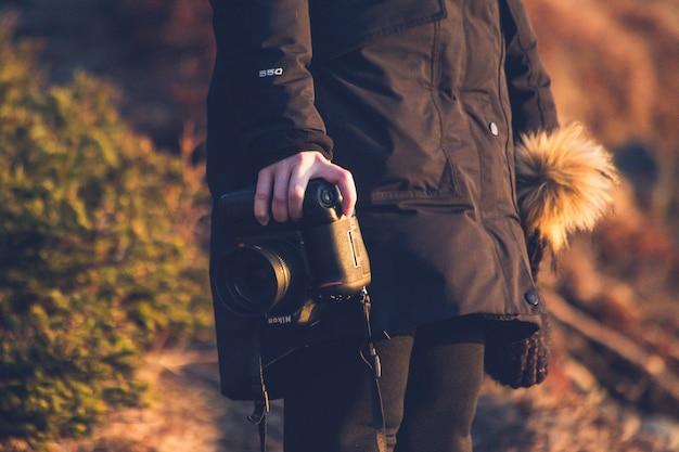 Person in der schwarzen jacke, die schwarze dslr-kamera hält
