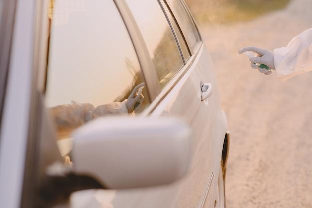 Person in einem schutzanzug desinfiziert das auto