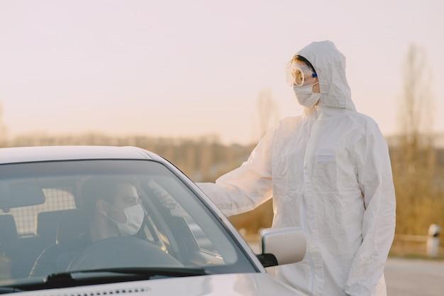 Person in einem schutzanzug überprüft die temperatur