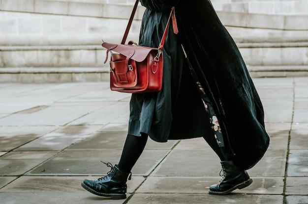 Person in einem schwarzen mantel, der umhängetasche trägt, während auf der straße geht