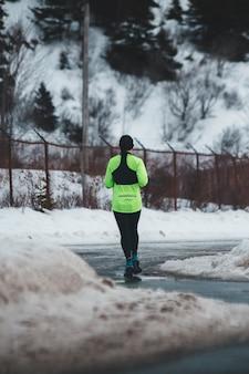 Person in grünem langärmeligem oberteil und schwarzer yogahose auf betonweg nahe schneebedecktem gelände tagsüber