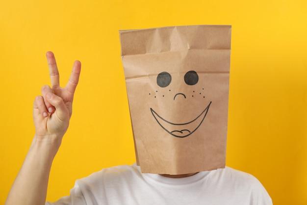 Person in papiertüte mit lächeln zeigen frieden auf gelb