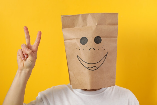 Person in papiertüte mit lächeln zeigen frieden auf gelber wand