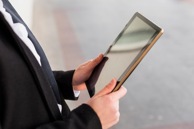 Person in schwarz mit tablet außerhalb