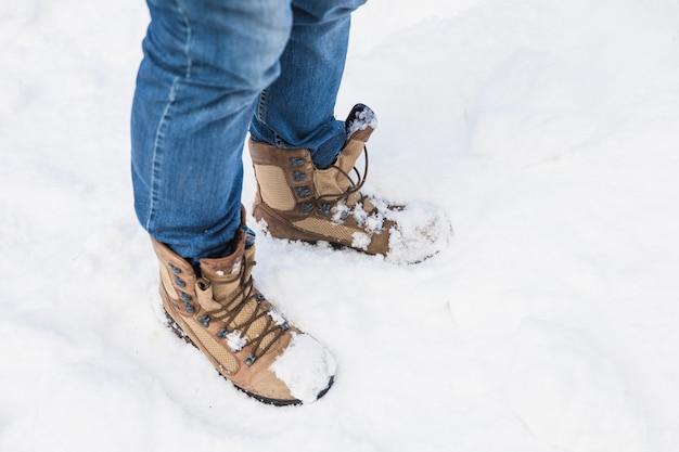 Person in stiefeln, die auf schnee stehen