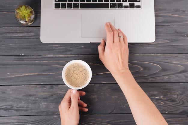Person mit dem kaffee, der bei tisch an laptop arbeitet