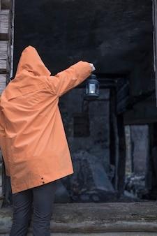 Person mit einer laterne schaut in ein altes zerstörtes niedergebranntes haus