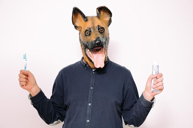 Person mit hundemaske, die bürste und zahnpasta hält