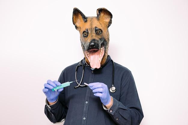 Person mit hundemaske, die eine spritze hält holding