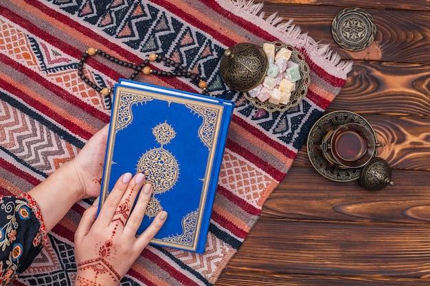 Person mit mehndi, die quran nahe türkischer freude hält