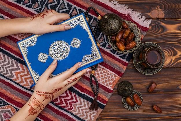 Person mit mehndi quran in der nähe von teetasse halten