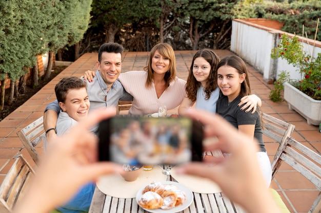 Person mit smartphone, die ein foto von der familie macht, die zusammen im freien zu mittag isst