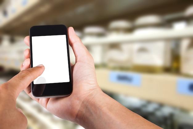 Person mit smartphone weißen bildschirm inhaber auf der hand mit verschwommenen hintergrund der chemikalien lagerung für probe versuche.