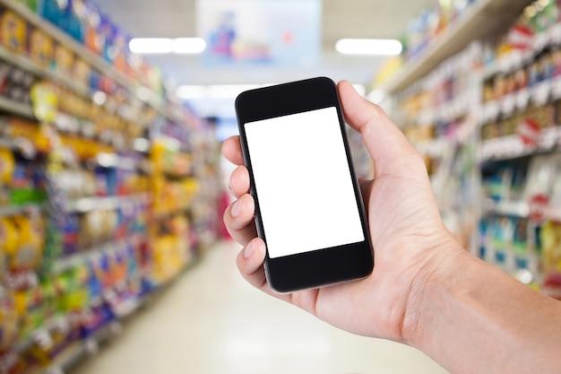 Person mit smartphone weißen bildschirmhalter auf der hand mit regalen auf hintergrund im supermarkt.