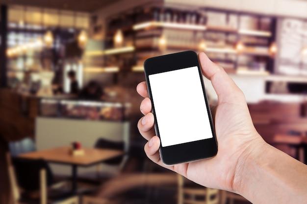 Person mit smartphone weißen bildschirmhalter auf der hand mit verschwommenen hintergrund des cafés.