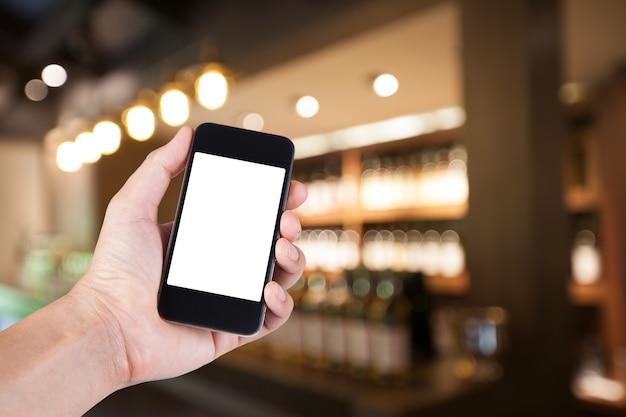 Person mit smartphone weißen bildschirmhalter auf der hand mit verschwommenen hintergrund von whisky-bar für erwachsene party auf restaurant.