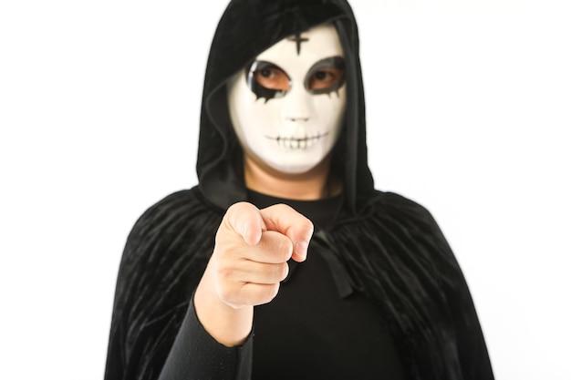 Person mit weißer maske mit kreuz auf der stirn und schwarzem samtumhang mit unscharfer kapuze, die mit fokussierter hand auf die kamera zeigt, auf weißem hintergrund. karneval, halloween und tag der toten konzept.