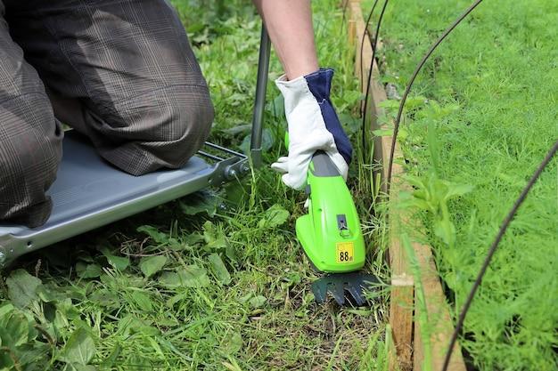 Person schneidet das gras auf dem weg in der nähe des gartens mit einem tragbaren elektrischen trimmer