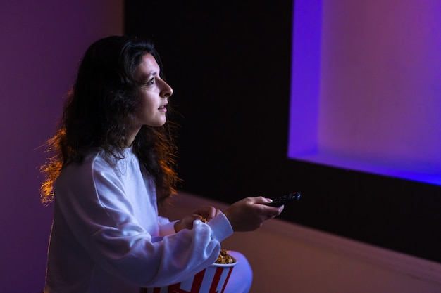 Person sieht einen film auf der couch mit einem eimer popcorn sitzen.
