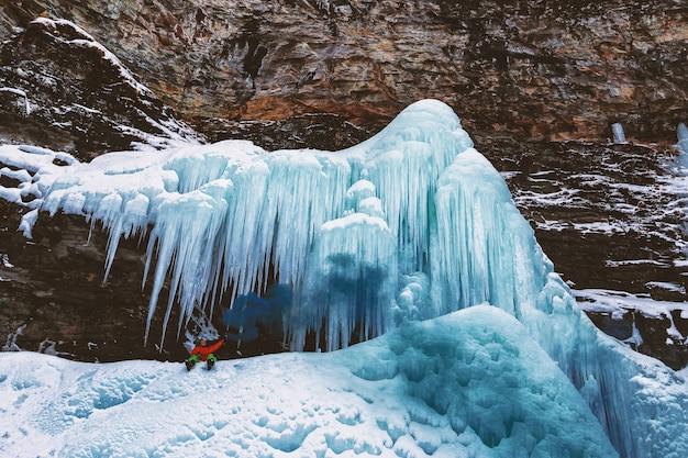 Person sitzt auf berg mit eiszapfen