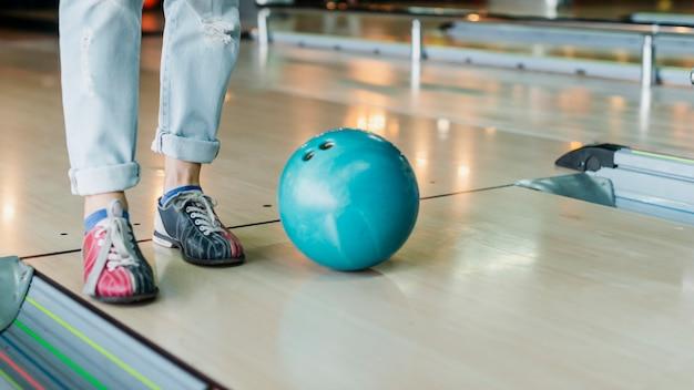 Person und bowlingkugel auf bowlingraum