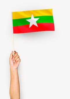 Person weht die flagge der republik der union von myanmar